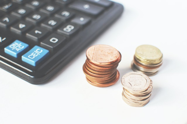tři komínky mincí, kalkulačka
